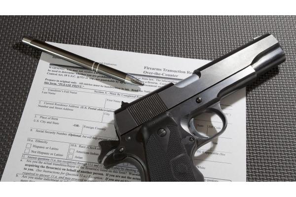 pistol on top of firearm transfer paperwork