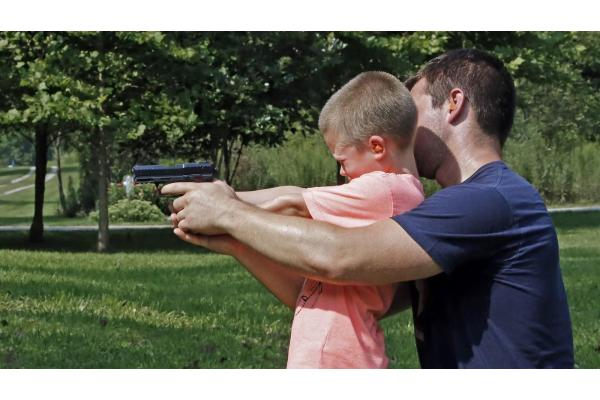man-teaching-son-to-shoot