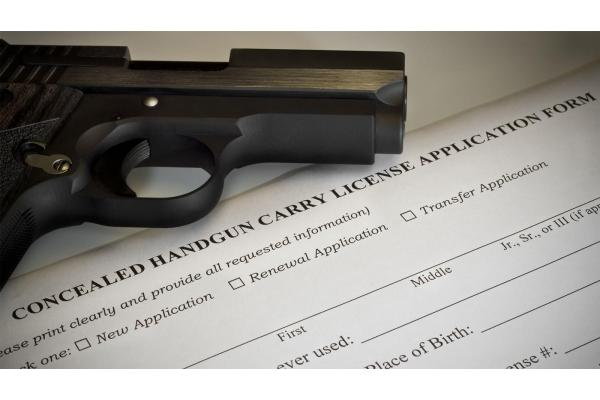 pistol sitting on a concealed carry permit application
