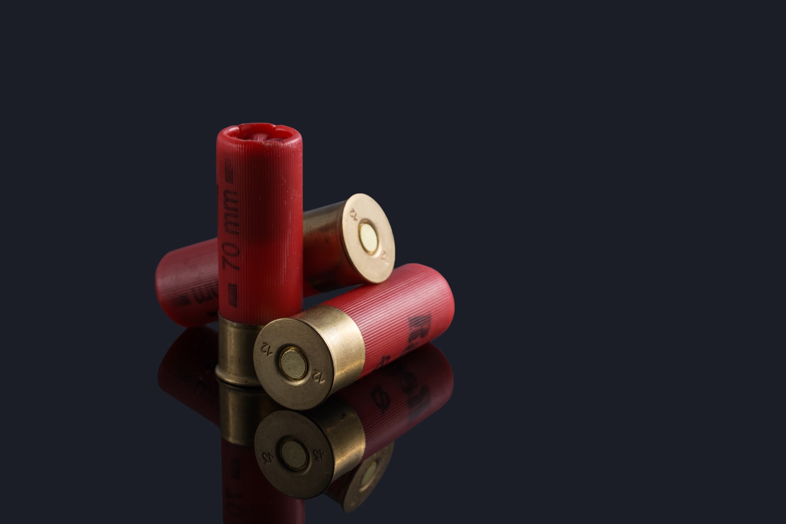 three 70mm red shotgun shells with a black background